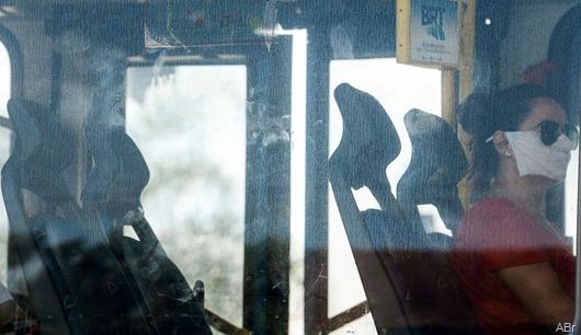 Passageira de ônibus BRT, aderem ao uso de máscaras descartáveis por precaução contra o coronavírus